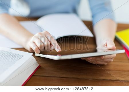 office, business, education, technology and internet concept - close up of student woman with tablet pc computer and notebook at home