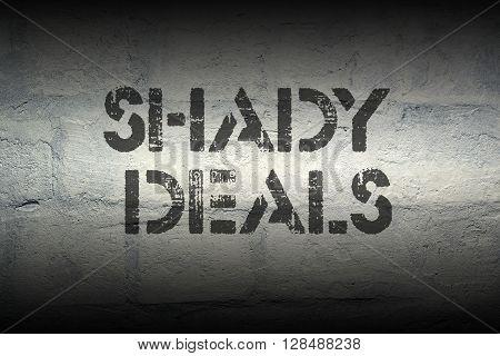 shady deals stencil print on the grunge white brick wall