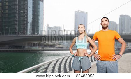 fitness, sport and healthy lifestyle concept - smiling couple exercising over dubai city street and waterside background