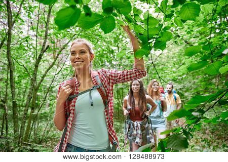 adventure, travel, tourism, hike and people concept - group of smiling friends walking with backpack