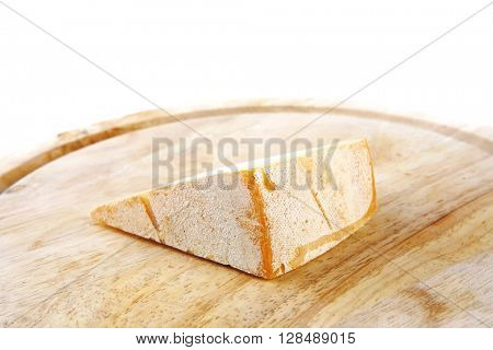 piece light swiss cheese on wooden board