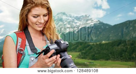 adventure, travel, tourism, hike and people concept - happy young woman with backpack and camera photographing over alps mountains background