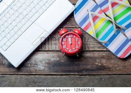 photo of the red clock laptop and colorful sandals on the brown wooden background