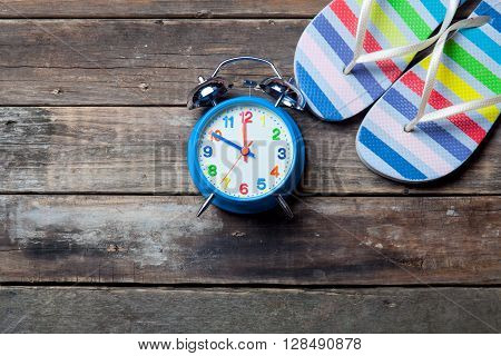 photo of the blue clock and colorful sandals on the brown wooden background