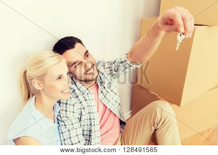 home, people and real estate concept - happy couple with key and cardboard boxes moving to new place