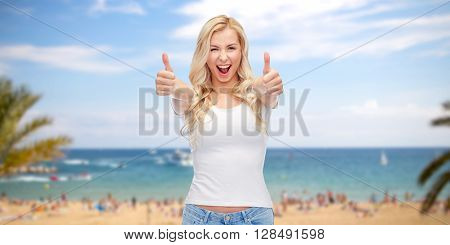 emotions, summer holidays, travel, advertisement and people concept - happy smiling young woman in white t-shirt showing thumbs up over exotic tropical beach with palm trees and sea background