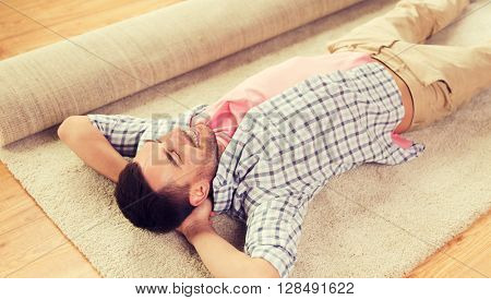 people, repair and renovation concept - happy man lying carpet or rug on floor at home