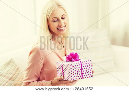 people, holidays, celebration and birthday concept - smiling young woman with gift box at home