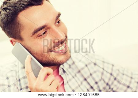 communication, technology and people concept - smiling young man calling on smartphone