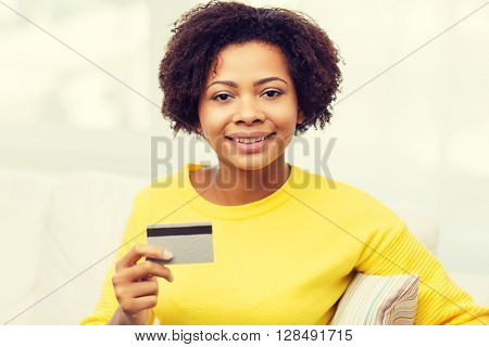 people, bank, shopping and e-money concept - happy african american young woman sitting on sofa with credit or debit card at home