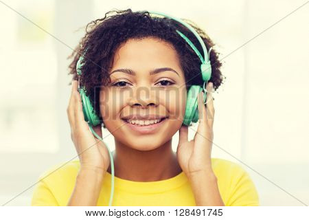 people, technology and leisure concept - happy african american young woman sitting on sofa with headphones listening to music at home