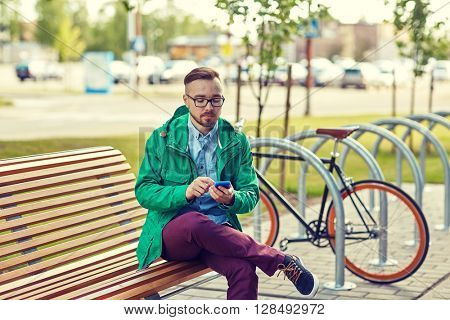 people, style, technology and lifestyle - happy young hipster man with smartphone and fixie bike sitting on bench in city