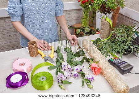 Florist at the shop. Accessories on the table