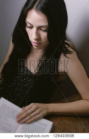 Young girl in negligee sitting at the desk and reading book in room