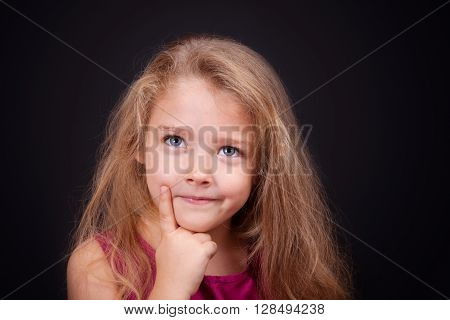 Little cute pensive girl in a bright pink dress on a black background in the studio