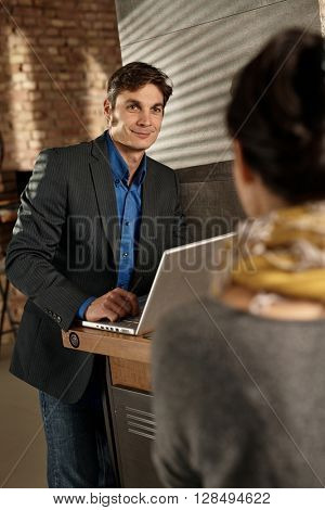 Businessman using laptop smiling at female colleague.