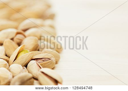 The pistachios on wood background. The pistachio background.