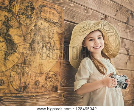 Go on an adventure! Cute child girl with vintage camera on wooden background wall and maps.
