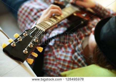 Young man with black hat playing electric guitar on grey sofa at home