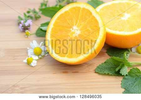 orange and lemon balm on wooden board