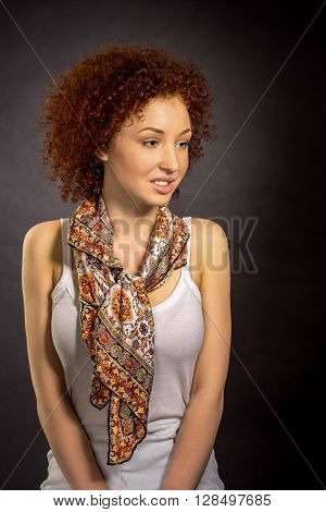 A Young Red Haired Woman In A Neckerchief Leaning Against A Gray Wall