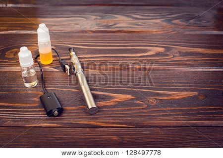 electronic nicotine inhalator on  background ,bottles with liquids behind the inhalator