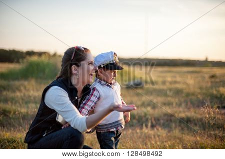 mother with child on a meadow near the forest
