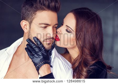 Sexy woman in gloves and red lips kiss young lover face indoor seduction
