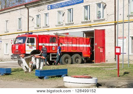 LODEYNOJE POLE, RUSSIA - MAY 2TH, 2016: Unidentified firefighters washing their fire truck next to the garage