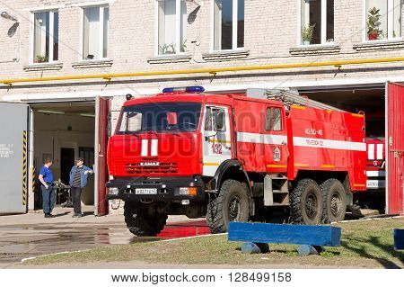 LODEYNOJE POLE, RUSSIA - MAY 2TH, 2016: Unidentified firefighters wait for a new assignment, and red fire truck in the garage