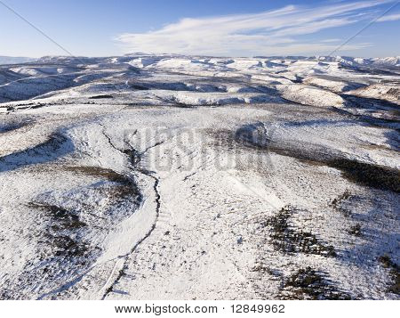 Aerial view of a snow-covered hills with sparse tree coverage. Horizontal shot.