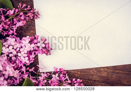 Bunch of lilac on brown wooden old table with blank paper page empty space for text. Lilac horizontal background. Happy Mothers Day. Mother's Day greetings card. Mothers Day gift. Toned image.