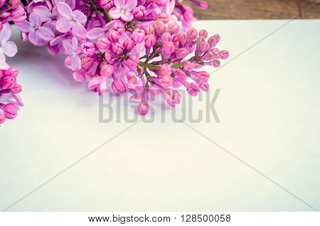 Bunch of lilac on brown wooden old table with blank paper page empty space for text. Lilac horizontal background. Happy Mothers Day. Mother's Day greetings card. Selective focus. Toned image.