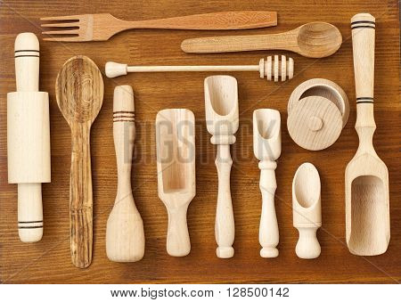 Set of the wooden kitchen utensils on wooden background. spoon mortar kitchen spatula rolling pin bowl fork. Overhead view of wood utensils on wood board background.