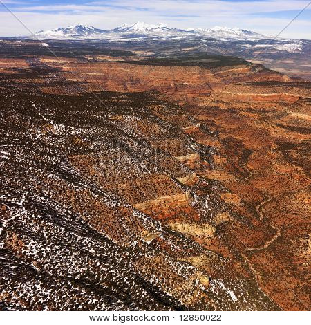 Aerial view of a of rural, desert landscape with mountains in the background and some snow scattered on the ground. Square shot.