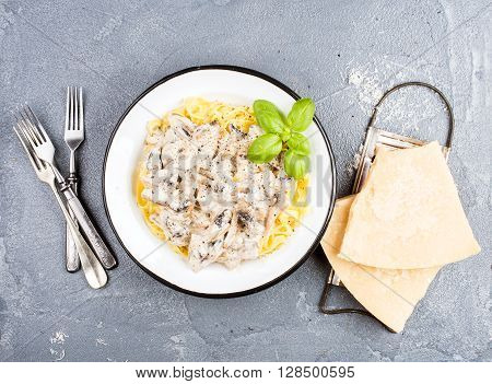 Tagliatelle pasta with mushrooms and creamy sauce, parmesan cheese over concrete textured background, top view