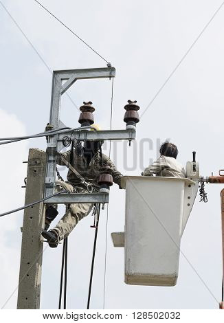 Two electrician are installing new cables of high voltage that one electrician is climbing on an electric power pole another one is on lift bucket