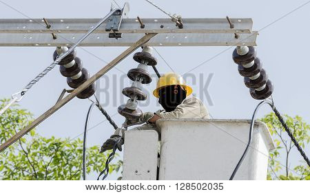 Close-up view of one electrician is repairing electric power system on an electric pole from lift bucket.