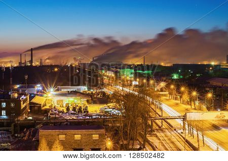Night landscape with a road in the industrial area of the city and the pipes metallurgical plant on the horizon. View from the top. City Nizhny Tagil. Russia