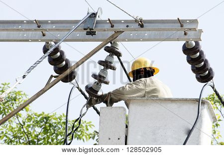 Close up view of one electrician is repairing electric power system on an electric pole from lift bucket.