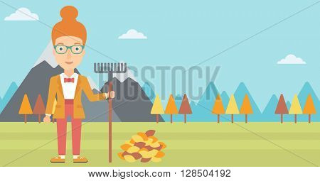 Woman with rake standing near heap of autumn leaves.
