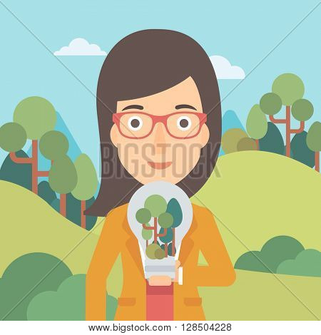 Woman with lightbulb and trees inside.