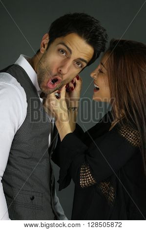 young woman pulling the ear of her boyfriend over a gray background