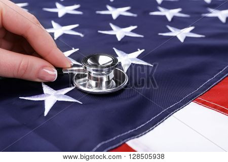 Female hand holding stethoscope on background of USA flag