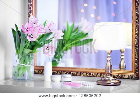 Bouquet of fresh tulips beside the mirror
