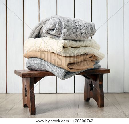 Stack of woolen clothes on wooden stool in a light interior