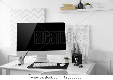 Modern wide screen monitor on white table in room interior