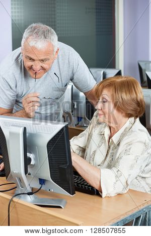 Senior Woman Showing Something To Classmate On Computer Monitor