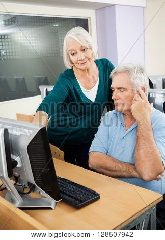 Woman Assisting Male Classmate In Computer Lab