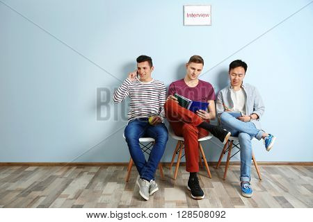 Three men waiting for interview indoors
